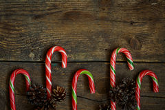 Christmas border with cones and candy cane on wooden boards Stock Photo
