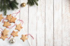 Christmas Border with cookies. Christmas star shaped gingerbread cookies with red ropes and balls for Christmas tree decoration on white shabby background, top royalty free stock photography