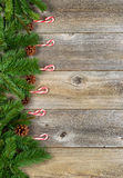 Christmas border with evergreen branches and candy canes on rust Royalty Free Stock Images