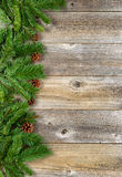 Christmas border with evergreen branches on rustic wooden boards Stock Photos