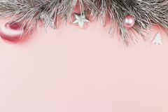 Christmas border with fir branches, christmas balls and silver ornaments on pastel pink background stock photo