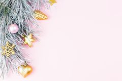 Christmas border with fir branches, conifer cones, christmas balls and golden christmas ornaments on pastel background Stock Photos