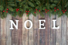 Christmas Border with Fir, Red Berries and Noel Letters Royalty Free Stock Images
