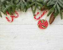 Christmas border with fir tree branches with cones and candy can Stock Photography