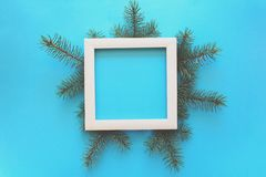 Christmas Border. Fir tree branches and white wooden frame on blue paper background. Top view. Copy space. Toned royalty free stock image