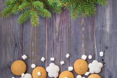 Christmas border with gingerbread, marshmallow and branch of fir tree Royalty Free Stock Photos