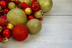 Christmas border of gold and red balls on a white wooden background. New year greeting card Copy space