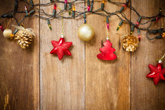 Christmas Border - golden baubles, stars, with light on old wood Stock Photos