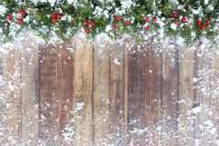 Christmas Border with Fir, Red Berries and Snow. Christmas border out of natural Christmas tree fir twigs and red berries on a brown wooden background covered in Royalty Free Stock Images