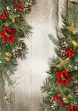 Christmas border with poinsettia, holly and fir branches on a wo. Christmas wood background with vintage border with Christmas decorations made of branches Royalty Free Stock Image