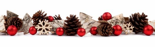 Christmas border with rustic wood tree ornaments, baubles and pine cones isolated over white. Christmas border with rustic wood tree ornaments, baubles and pine Royalty Free Stock Photography