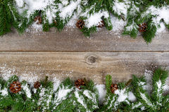 Christmas border with snow covered branches on rustic wooden boa Stock Photos