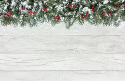 Christmas Border with Snow Covered Red Berries and Fir. Christmas border out of natural Christmas tree fir twigs and red berries on a gray wooden background Royalty Free Stock Photography