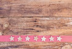 Christmas border with stars ornaments on red ribbon border and rustic wooden background Royalty Free Stock Photography