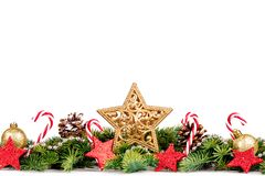 Christmas Border - tree branches with golden balls, candy and big star isolated on white. Horizontal banner stock photo