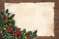 Christmas Border. Christmas and winter background border with fir, holly, ivy, mistletoe and pine cones over old parchment paper and oak wood royalty free stock photos