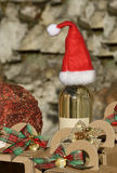 Christmas bottle. Bottle of white wine with hat of Santa Claus royalty free stock images
