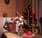 Christmas bouquet of red roses. Flowers, cotton and green spruce branches, and the candlestick with red candles on the background of Christmas tree stock images