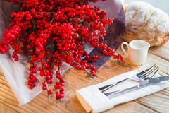 CHRISTMAS BOUQUET OF RED WINTERBERRY FLOWERS ON A WOODEN TABLE. Red ilex flowers on wooden table with a bread, a creamer and fork on a napkin Royalty Free Stock Images