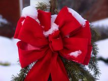 Christmas Bow. On wreath in front of house in snow stock photos