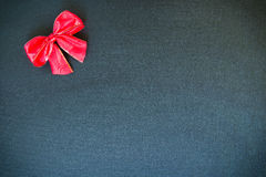 Christmas bow on a black canvas background. Christmas holiday bow made of red ribbon on a black canvas background with copy space Stock Photography