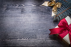 Christmas bow pine branch giftbox on wooden board Royalty Free Stock Photos