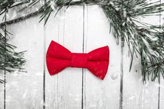 Christmas bow tie decoration with snow on white wooden background. Holiday New Year postcard design.  stock photo
