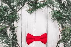 Christmas bow tie decoration with snow on white wooden background. Holiday New Year postcard design.  royalty free stock photos