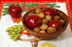Christmas bowl. Apples and nuts in a bowl lying on the christmas table Royalty Free Stock Photo