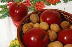 Christmas bowl. Apples and nuts in a bowl lying on the christmas table Stock Image