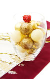Christmas bowl with golden baubles. Celebrating Christmas at dinner table with bowl of golden baubles and red sparkling heart. Isolated on white Royalty Free Stock Photography