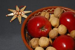 Christmas bowl and star. Apples and nuts in a bowl with a star made of straw Royalty Free Stock Photography