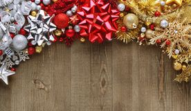 Christmas bows, ornaments, and decorations on wooden. Background Royalty Free Stock Photos