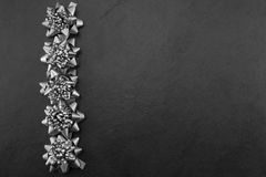 Christmas Bows. Pewter/silver Christmas bows on a slate background Stock Images