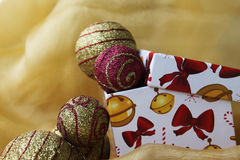 Christmas box. Handmade gift box with christmas balls,  on yellow cloth Royalty Free Stock Photos