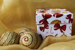Christmas box. Handmade gift box with christmas balls,  on yellow cloth Royalty Free Stock Photo