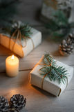Christmas box and burning candle. Boxes with Christmas presents on wooden surface against defocused lights Royalty Free Stock Photography