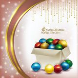 Christmas box with colored balls on pink background Stock Photo