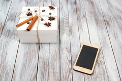 Christmas box decorated by cinnamon, anise, coffee, beans and phone on wooden background.Winter holidays concept. Space for text. royalty free stock photo