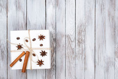 Christmas box decorated by cinnamon, anise, coffee, beans on wooden background.Winter holidays concept. Space for text. Royalty Free Stock Photography