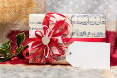 Christmas box (package) with blank gift tag. Christmas box with white paper, red ribbon and blank gift tag Royalty Free Stock Images