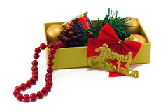 Christmas box with toys on white. Christmas box with golden balls, strobile, beads and red drum on white Royalty Free Stock Photo