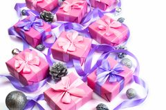 Christmas boxes with gifts on the occasion of pink color on white background cones nuts decor Top view flat lay horizontal. Christmas boxes with gifts on the stock image