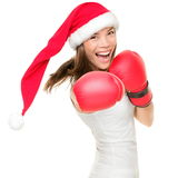Christmas boxing woman. Christmas woman hitting wearing boxing gloves and red santa hat. Shopping boxing day or fitness concept. Beautiful fresh energy from Stock Photography