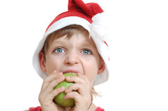 Christmas boy biting an apple Royalty Free Stock Images