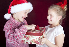 Christmas boy giving present to smiling girl. Over dark Royalty Free Stock Images