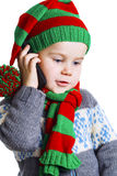 Christmas boy in knitted cloths makes a phone call to Santa Claus. Little boy in a knitted hat, scarf and sweater makes a phone call to Santa Claus with a stock photo