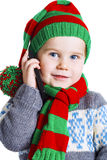 Christmas boy in knitted cloths makes a phone call to Santa Claus. Little boy in a knitted hat, scarf and sweater makes a phone call to Santa Claus with a stock photography