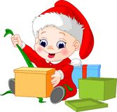 Christmas_boy_open_gift. Little boy in christmas hat open gift Royalty Free Stock Image