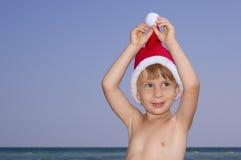 Christmas boy play on the beach. Funny Christmas boy play on the beach Stock Photos